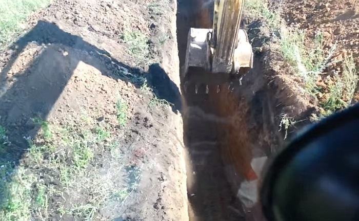 Экскаватор копает траншею в Троицком округе